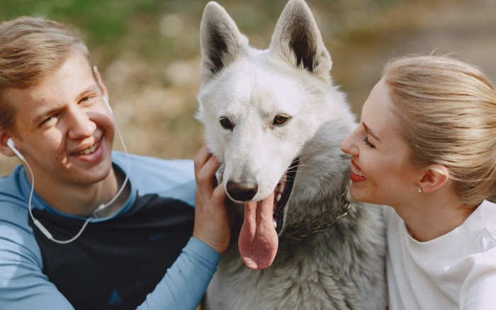 two people with a friendly dog
